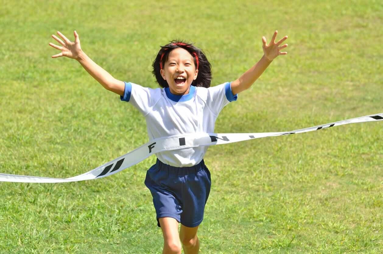 A young Asian girl winning a race.